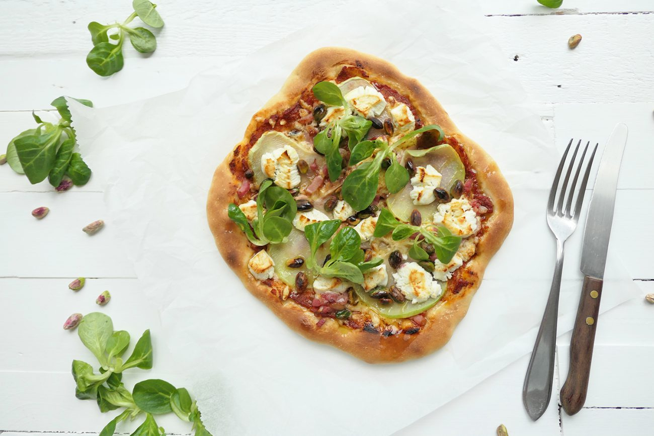 Spelt Pizza with homemade sauce and a topping of kohlrabi, goat cheese, pistachio nuts and corn salad